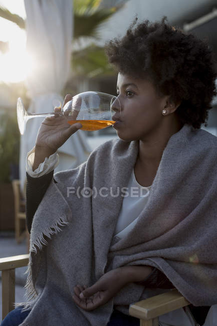 Young woman sitting in bar drinking aperitif — Stock Photo