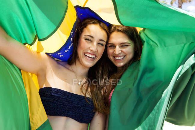 Two friends wearing beachwear playing with Brazilian flag — Stock Photo