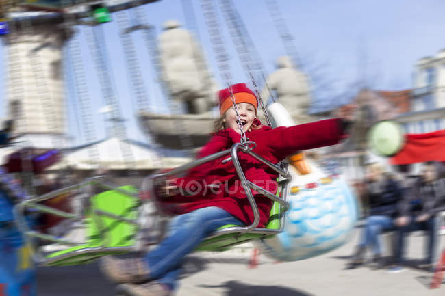 Happy little girl on chairoplane at fun fair — Stock Photo
