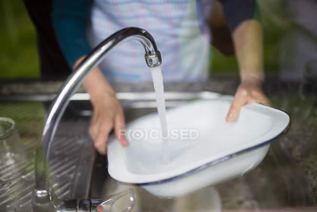 Mujer lavando platos en fregadero de cocina - foto de stock
