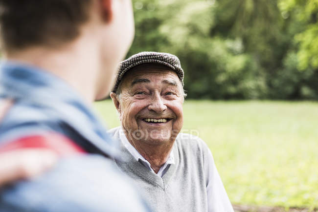 Portrait of senior man talking with his grandson — Stock Photo