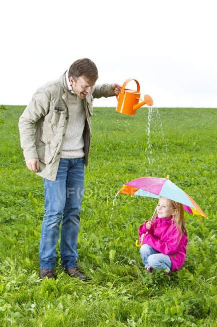 Pai com regador e filha com guarda-chuva no prado — Fotografia de Stock