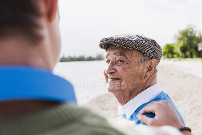 Portrait of smiling senior man looking at his grandson — Stock Photo