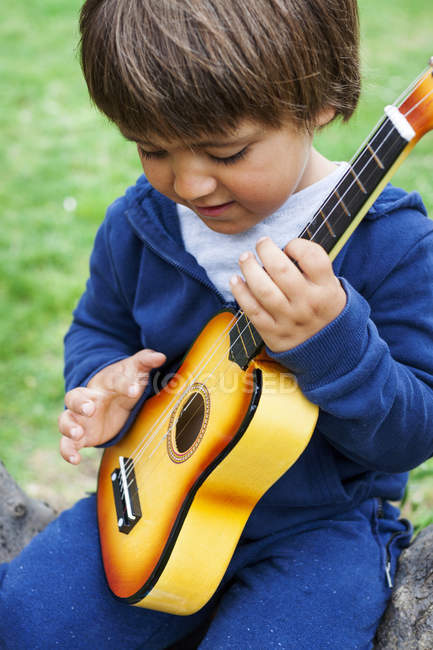Little cute boy playing guitar outdoors — Stock Photo