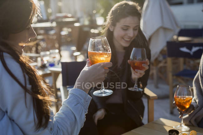Young women sitting in bar drinking aperitif — Stock Photo