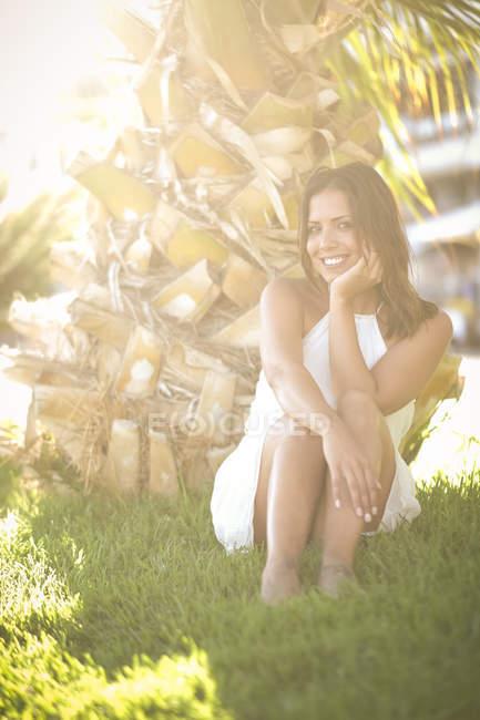 Jovem sorridente sentada à sombra de uma palmeira — Fotografia de Stock