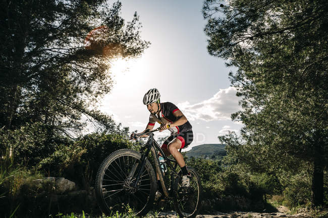Mountain biker in movimento in retroilluminazione — Foto stock