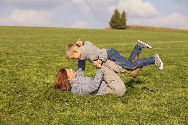 Madre e figlio spensierati che giocano nel prato — Foto stock