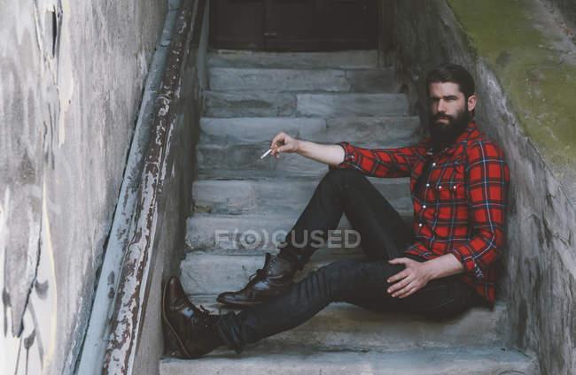 Портрет серьезного человека с сигаретой, сидящего на лестнице — стоковое фото
