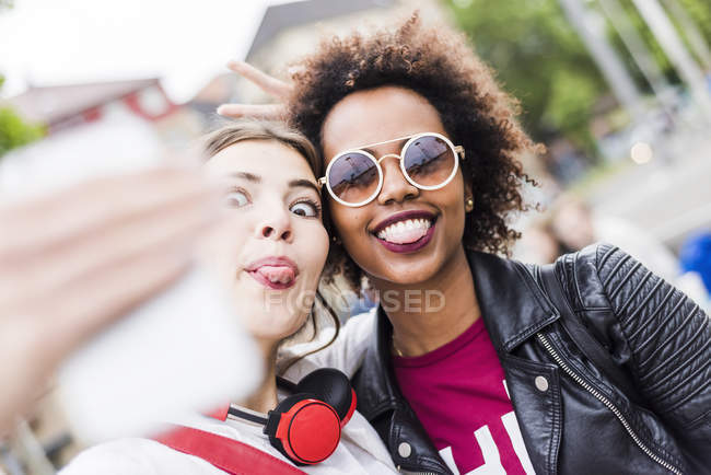 Two women sticking out tongues while taking selfie with smartphone — Stock Photo