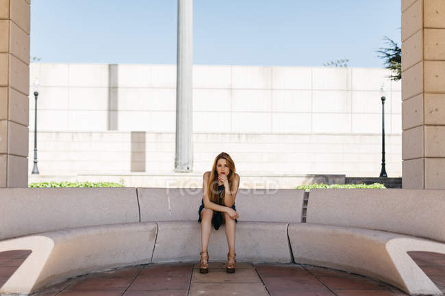 Spain, Barcelona, pensive woman resting on a bench in the shade — Stock Photo