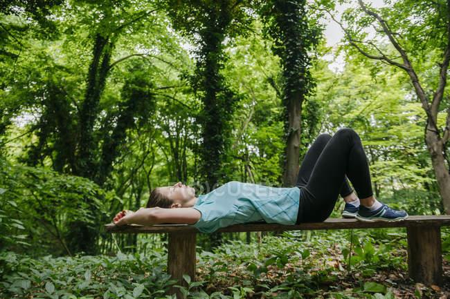 Молодая женщина отдыхает на скамейке в лесу — стоковое фото