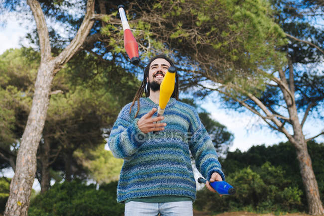 Young man with dreadlocks juggling with juggling clubs — Stock Photo