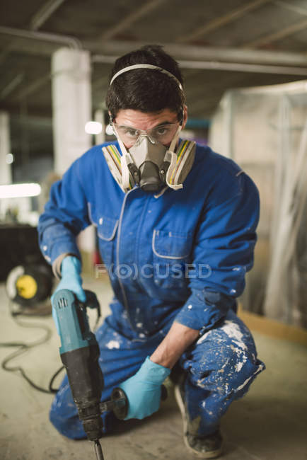 Bricklayer removing irregularities on floor screed with jackhammer — Stock Photo