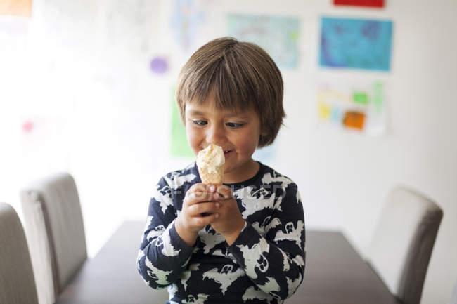 Ritratto di bambino con gli occhi incrociati e cono gelato — Foto stock