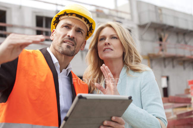 Man with hard hat discussing with woman on construction site — Stock Photo