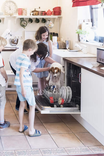 Family and dog in kitchen at dishwasher — Stock Photo