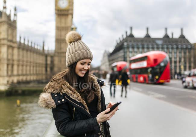 Reino Unido, Londres, sorrindo jovem olhando para seu smartphone na frente do Palácio de Westminster — Fotografia de Stock
