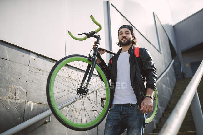 Joven llevando bicicleta fixie - foto de stock