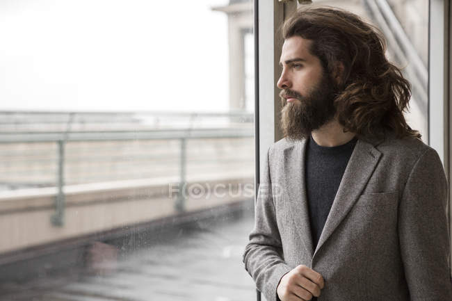 Pensive bearded businessman looking through window — Stock Photo