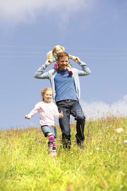 Счастливые отец и дочь гуляют с куклой на лугу — стоковое фото