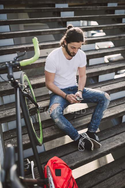 Молода людина, сидячи на сходах, дивлячись на смартфон — стокове фото