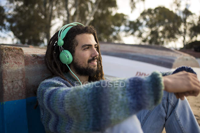 Young man with dreadlocks listening to music with headphones — Stock Photo
