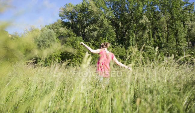 Back view of teenage girl on a meadow — Stock Photo