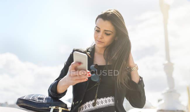 Jovem mulher usando smartphone ao ar livre — Fotografia de Stock