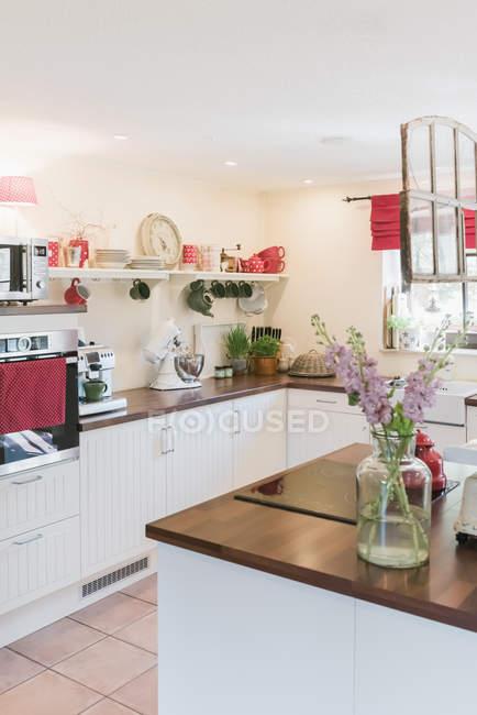 Cozinha com flores na ilha de cozinha dentro de casa — Fotografia de Stock