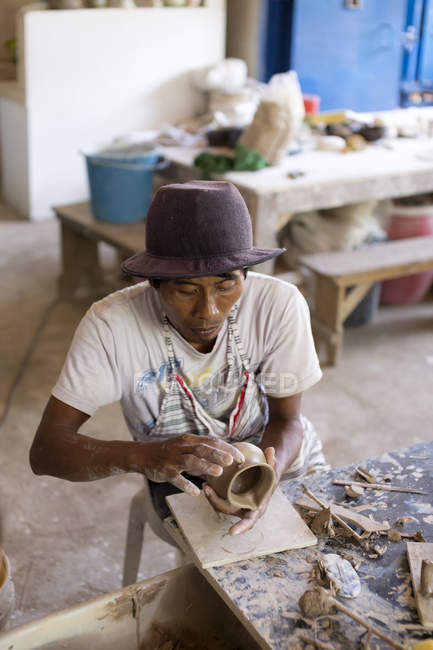 Potter in workshop working on earthenware jar — Stock Photo