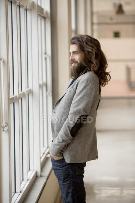 Hipster giovane uomo d'affari che osserva dalla finestra sorridente — Foto stock