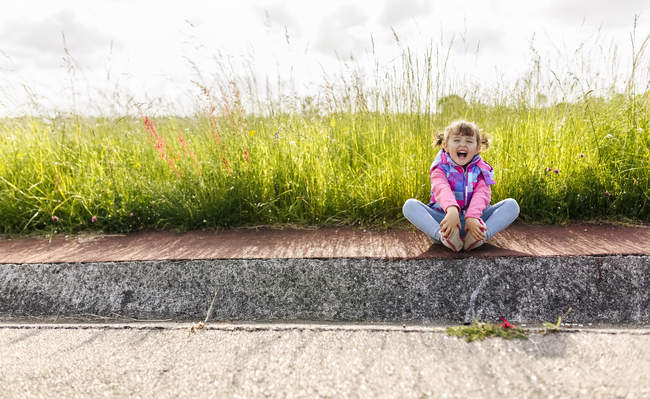 Laughing little girl sitting on pavement in front of a meadow — Stock Photo