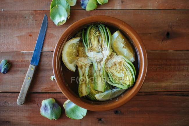 Pot en argile avec des artichauts en tranches dans de l'eau avec du citron — Photo de stock