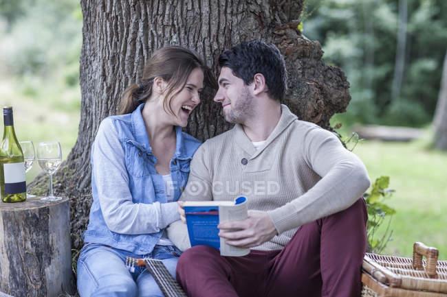 Feliz pareja joven haciendo un picnic con vino blanco - foto de stock