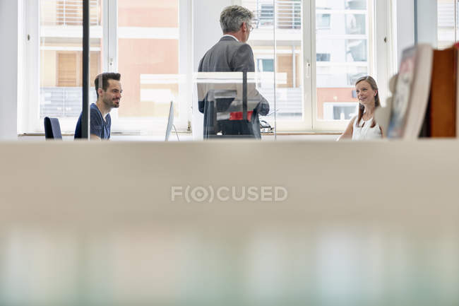 Adult manager discussing with coworkers in office — Stock Photo