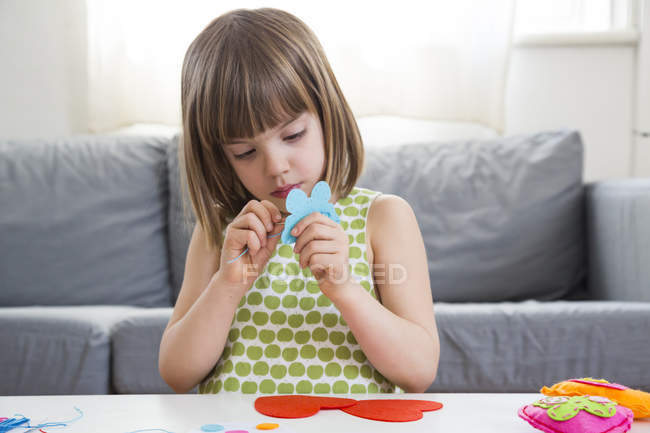 Portrait of embroidering serious girl at table indoors — Stock Photo