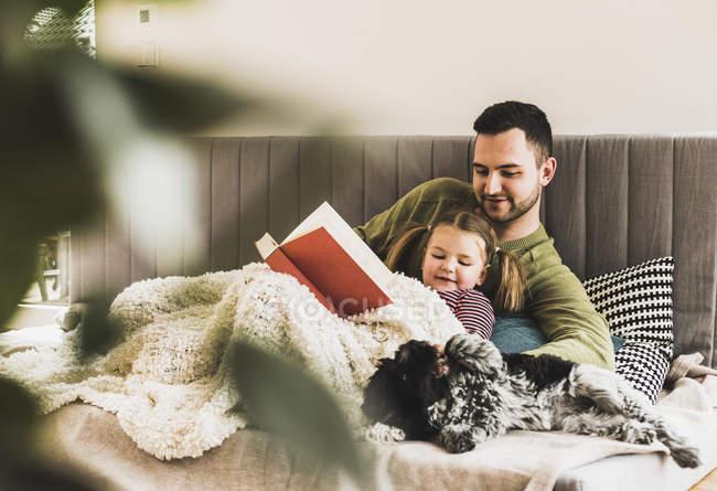 Pai e filha com cão lendo um livro em casa — Fotografia de Stock