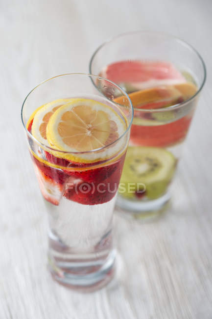 Dois copos de água aromatizados com frutas diferentes — Fotografia de Stock