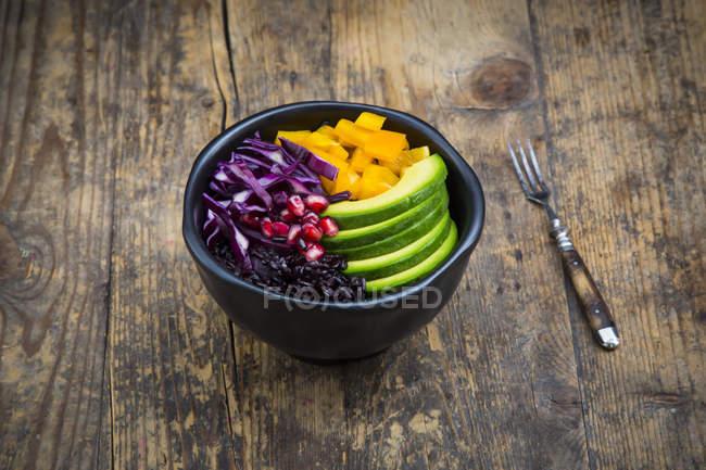 Чаша з чорний рис, авокадо, жовтий перець болгарський, Червона капуста і Гранат насіння по дереву — стокове фото