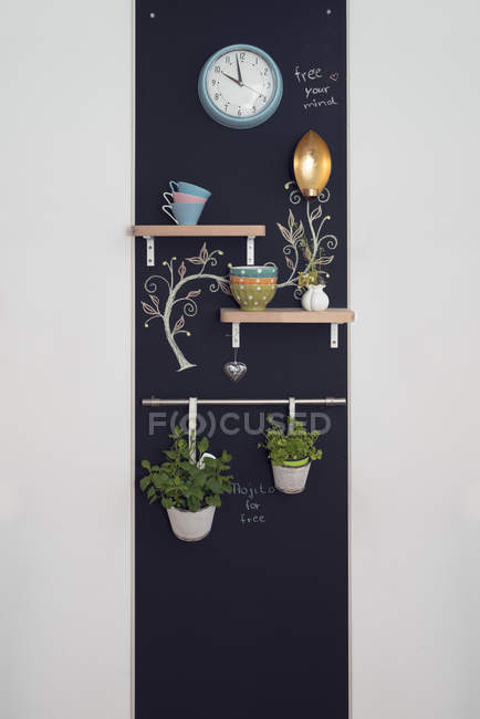 Wall decoration with shelves and herbs on blackboards with lamp and clock — Stock Photo