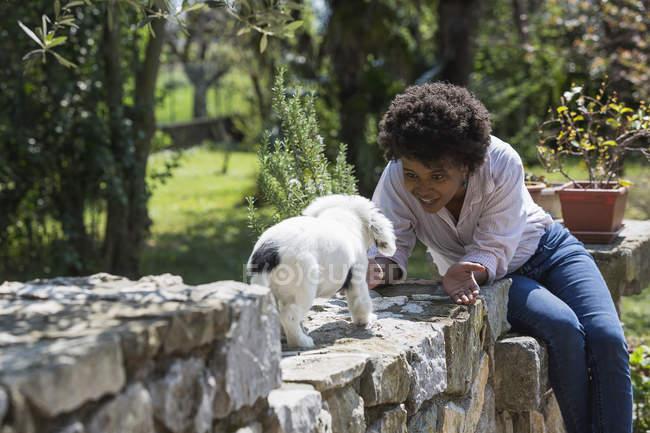 Femme jouant avec chien sur mur de pierre — Photo de stock