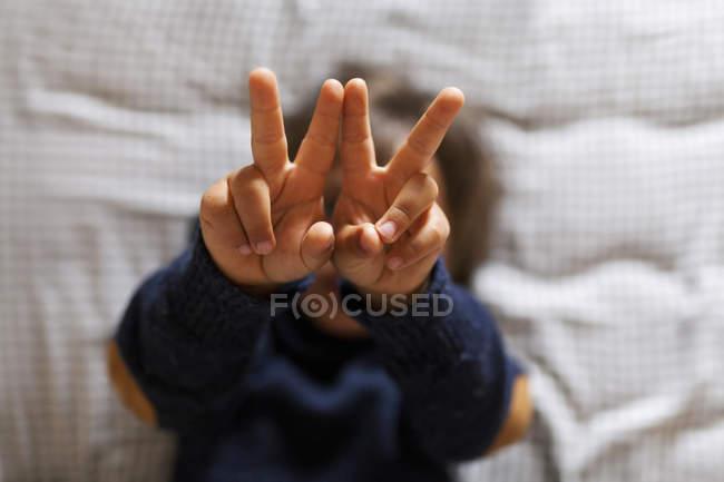 Menino fazendo sinal de vitória com as mãos — Fotografia de Stock