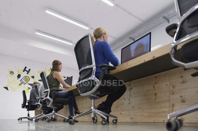 Employés travaillant dans des ordinateurs dans un bureau moderne — Photo de stock