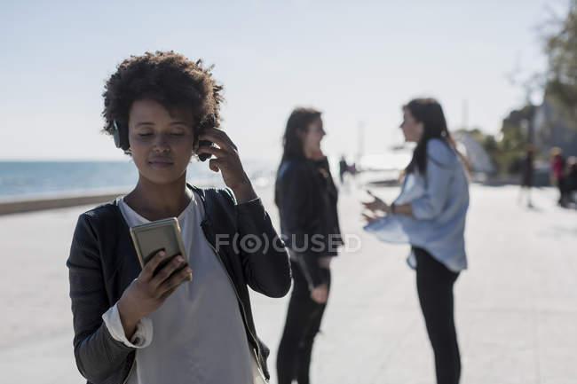 Jovem mulher ouvindo música com telefone inteligente — Fotografia de Stock