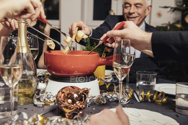 Друзья едят сырное фондю в канун Нового года — стоковое фото