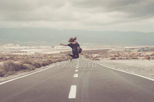 Young woman jumping for joy on a road — Stock Photo
