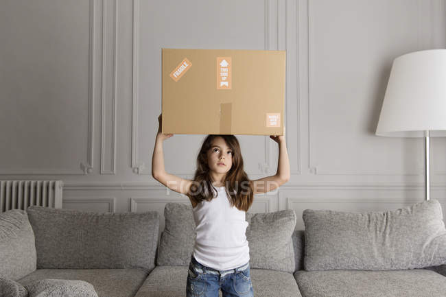 Girl holding a cardboard box on top of her head at home — Stock Photo