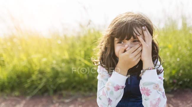Porträt eines kleinen Mädchens, das den Mund mit der Hand bedeckt, während es etwas beobachtet — Stockfoto