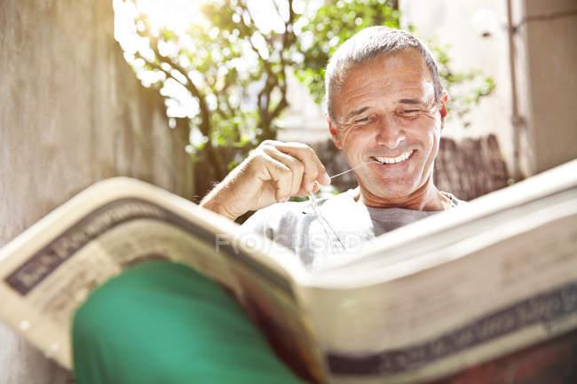 Portrait of smiling man reading newspaper — Stock Photo